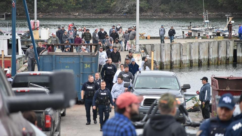Des policiers circulent à travers un groupe de personnes sur un quai.