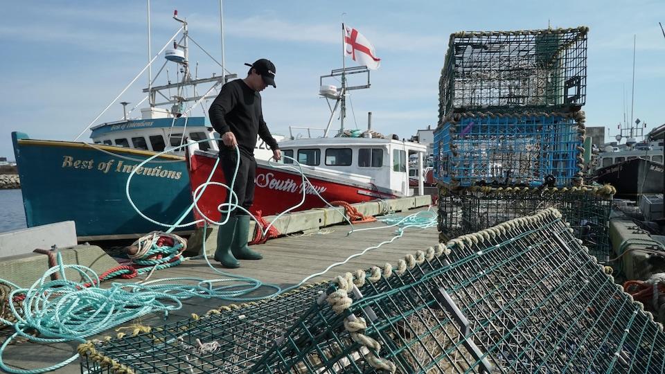 Pêcheur sur le quai avec des cordages et des casiers à homard.