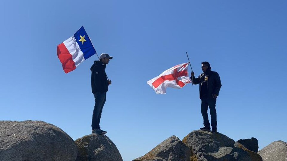 Deux hommes debout, chacun sur un rocher. Ils se font face. L'un a un drapeau acadien et l'autre, un drapeau micmac.