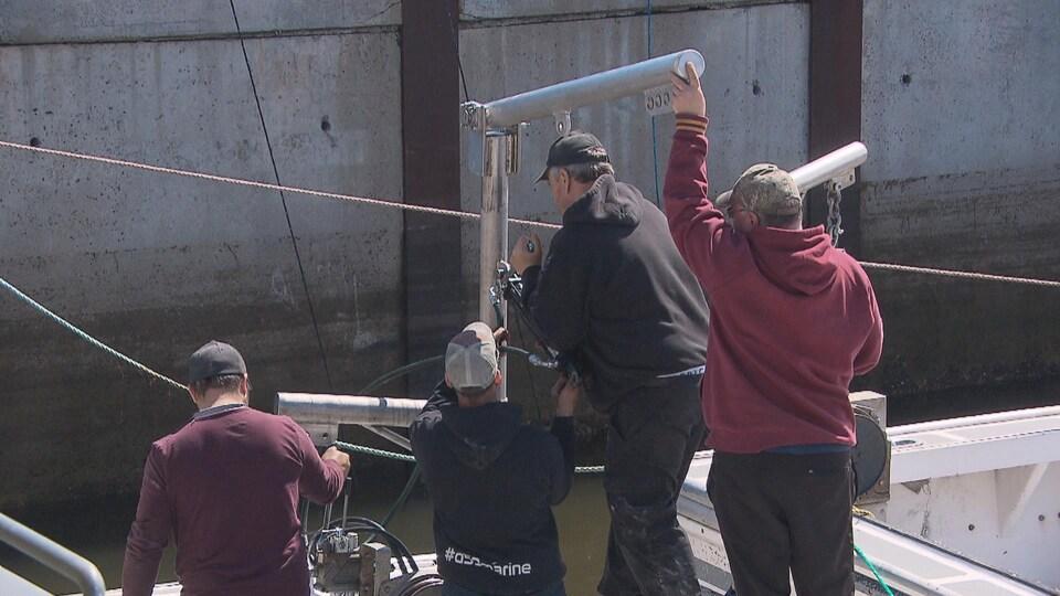 Quatre membres d'un équipage de bateau, photographiés de dos, installent une pièce métallique.