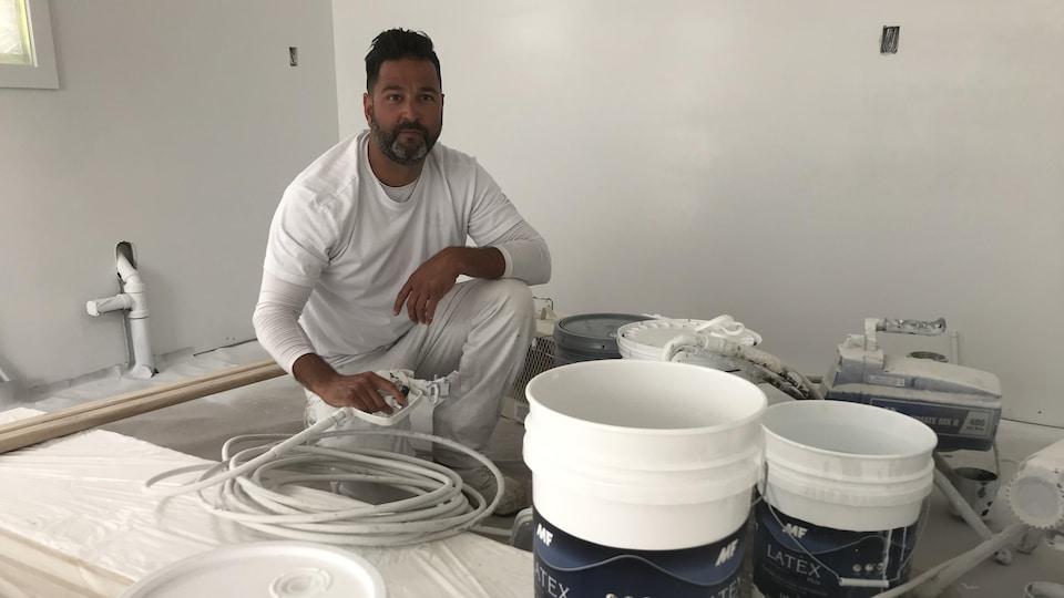 Un homme se tient au milieu de son équipement pour peindre.