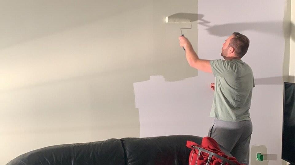 Un homme peinture un mur avec un rouleau.