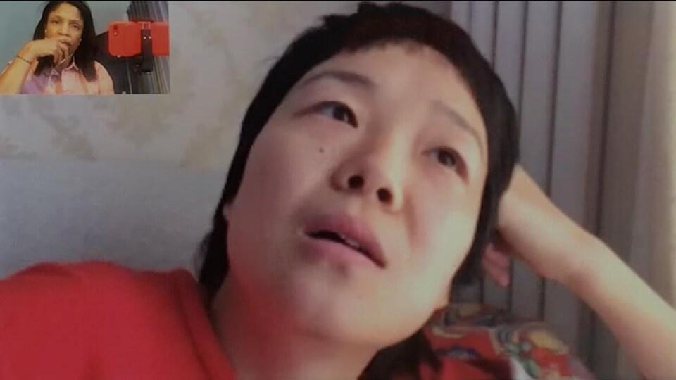 Une femme, en conversation par lien vidéo, la tête appuyée sur sa main.