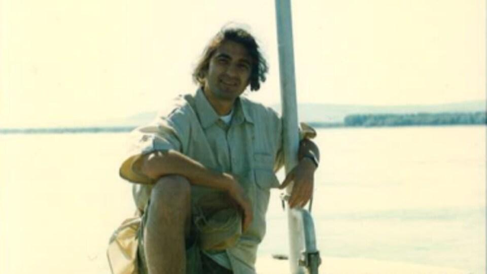 Un homme dans la vingtaine est assis sur le pont d'un bateau.