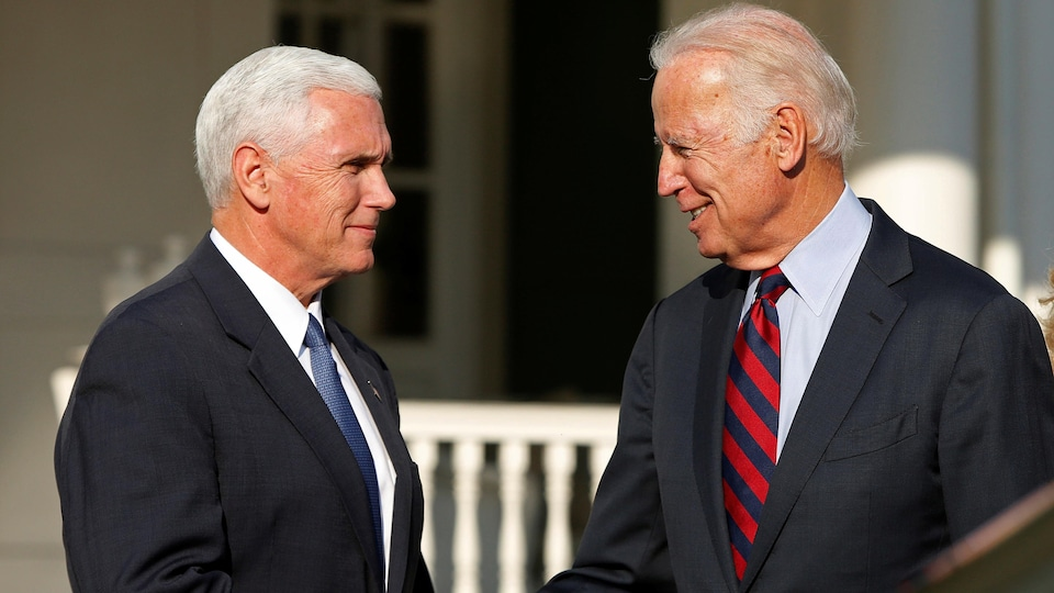 Joe Biden et Mike Pence, souriant, l'un face à l'autre