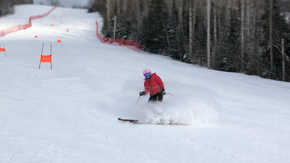 Une skieuse en train de freiner au bas d'une pente de slalom.