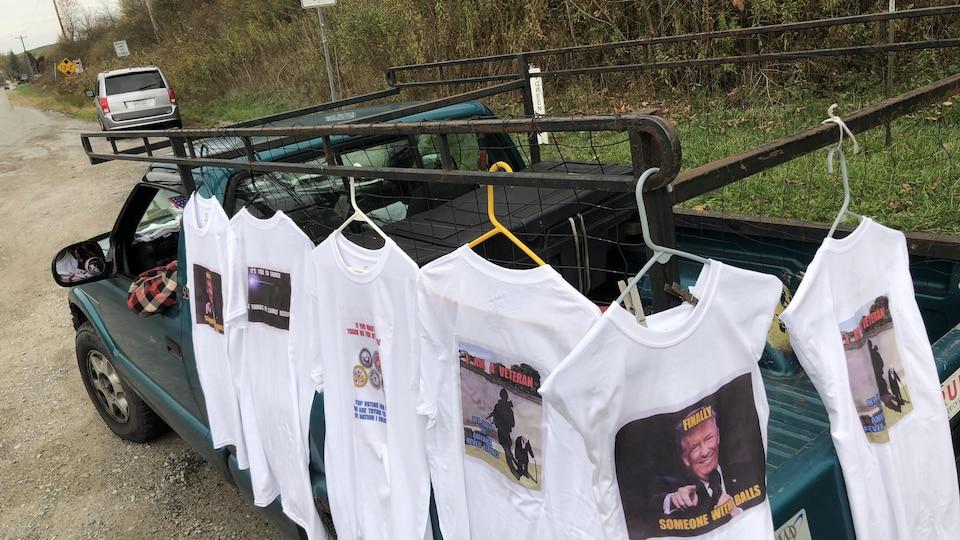Des chandails blancs imprimés accrochés à une voiture.