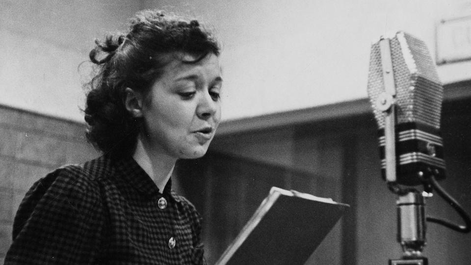 Dans un studio de radio, la comédienne Estelle Mauffette au micro avec son texte à la main.