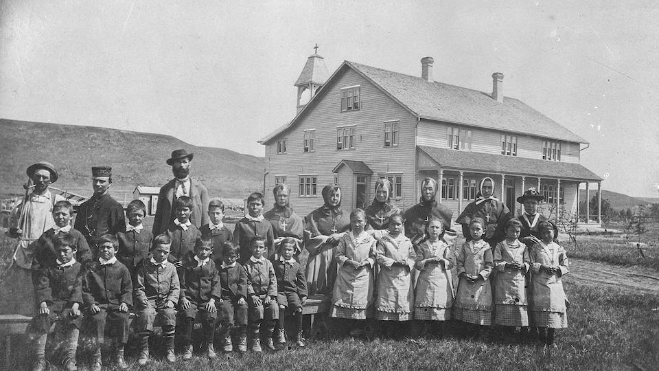 Des élèves de la Première Nation Blackfoot regroupés devant le pensionnat autochtone à vocation industrielle Saint Joseph (aussi appelée Dunbow), à l'est de High River, en Alberta, en 1888.