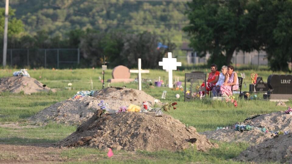 Des amas de terre sur un vaste terrain où se trouvent des tombes.