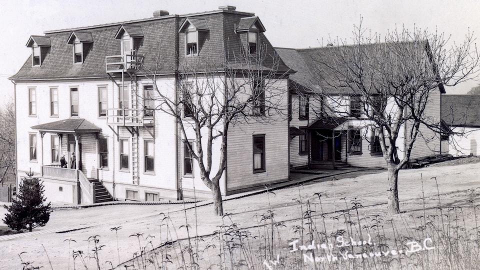 Un bâtiment de bois de deux étages comprenant plusieurs ailes et dont le toit est mansardé.