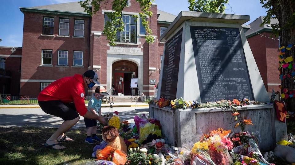 Des gens posent des fleurs devant un momument commémoratif à la mémoire des anciens pensionnaires autochtones à Kamloops.