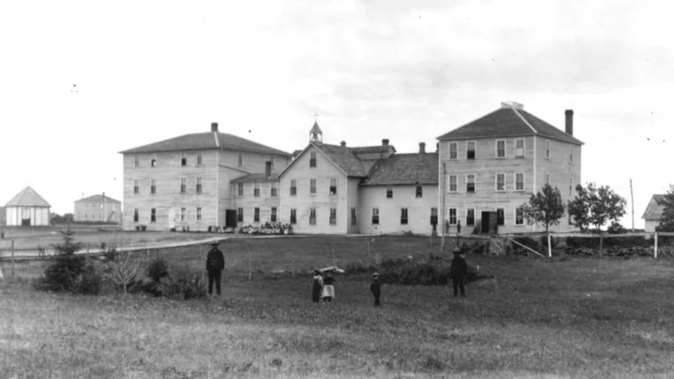Une photo d'époque.  Quelques enfants et deux adultes se trouvent devant le pensionnat Thunderchild, l'été.