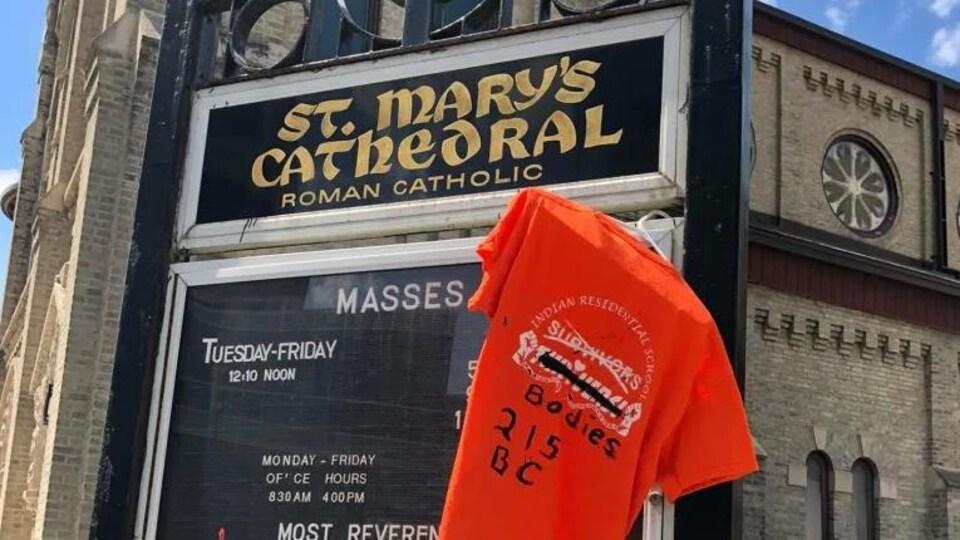 Un chandail orange accroché devant une église.