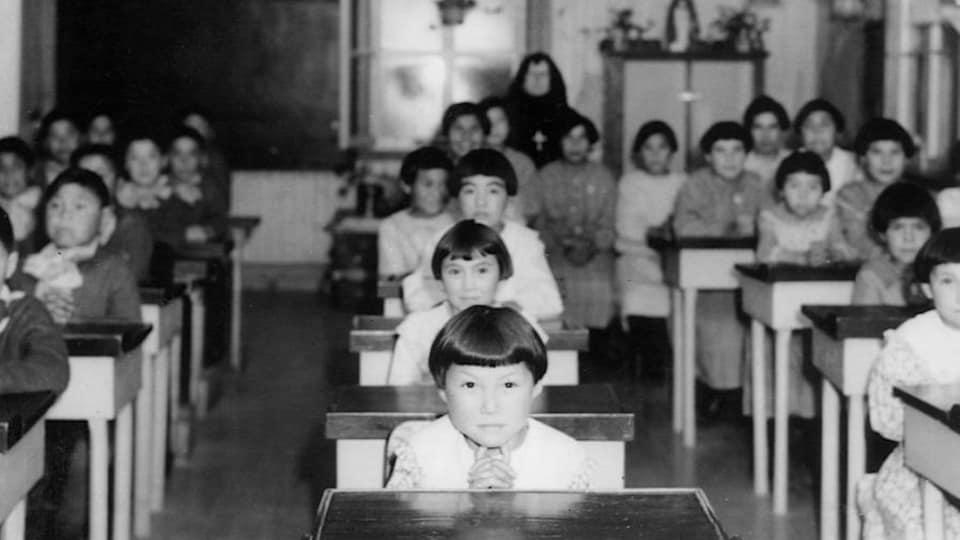 Des enfants autochtones sont assis à leur pupitre dans la salle de classe d'un pensionnat autochtone, à la fin des années 1930.