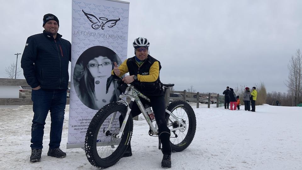 Deux hommes, dont un sur un vélo, posent devant une affiche de la Fondation Arianne.