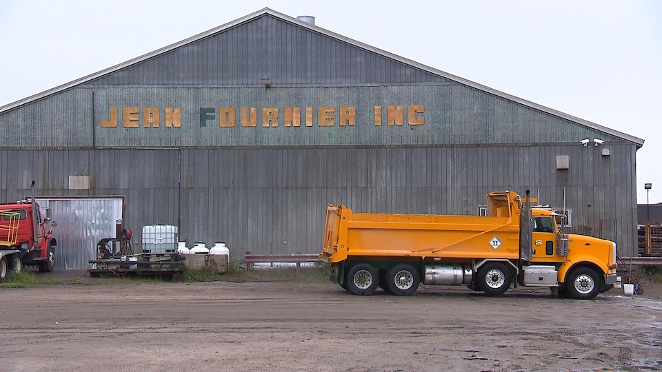Un camion-benne est stationné devant le bâtiment de l'entreprise Jean Fournier inc.
