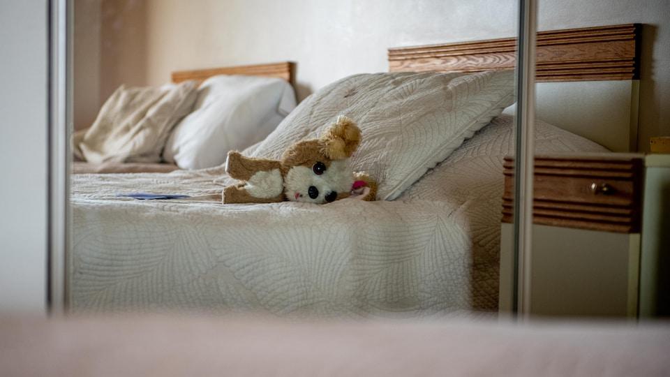 Une peluche sur un lit dans un hôtel.