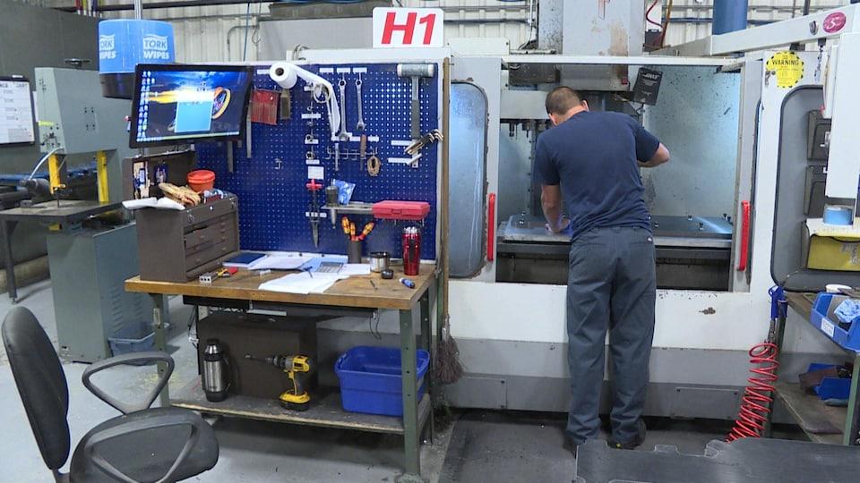 Une personne travaille sur une machine, en intérieur.