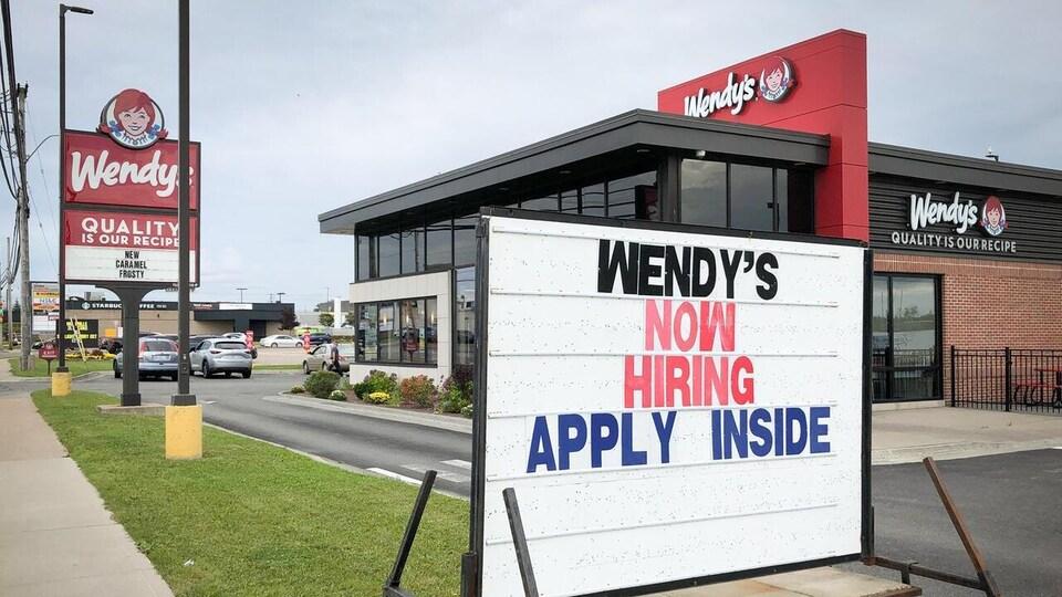 Une affiche devant un restaurant Wendy's invite les gens à postuler à un emploi.