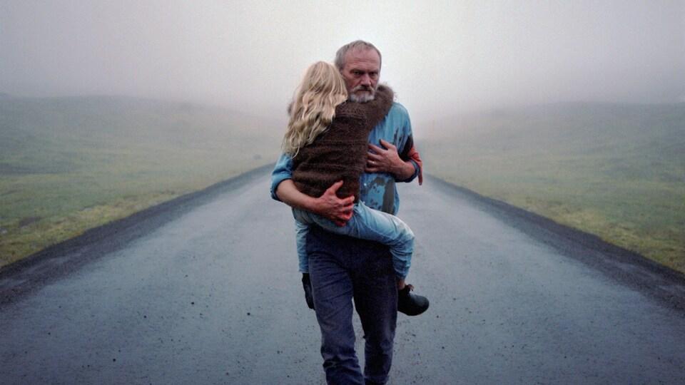 Une homme triste avance sur un chemin avec une petite fille dans ses bras.