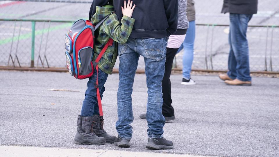 Un enfant enlace son père dans la cour d'école.