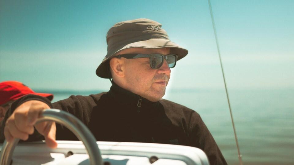 Le père de Kevin-Koudbi portant un chapeau et des verres fumés sur un bateau.