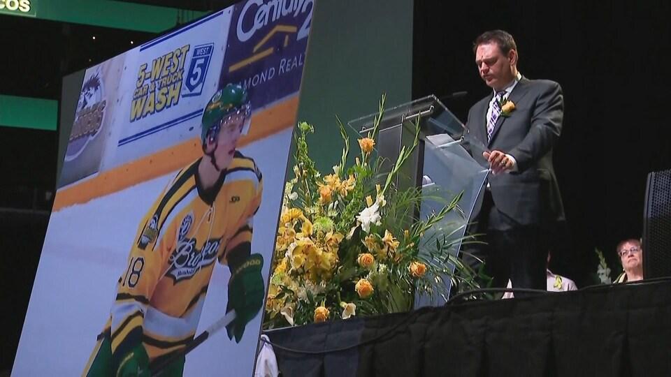 Le père de Logan Hunter, Lawrence Hunter, au podium devant une photo de son fils en tenue de hockey.
