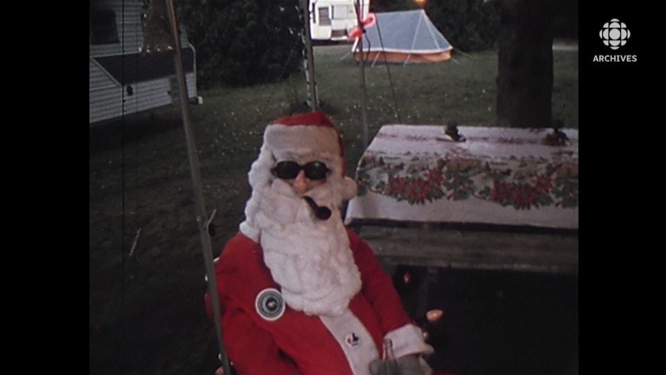 Un mannequin déguisé en père Noël est assis sur un site de camping, sous la toile d'une tente roulotte.