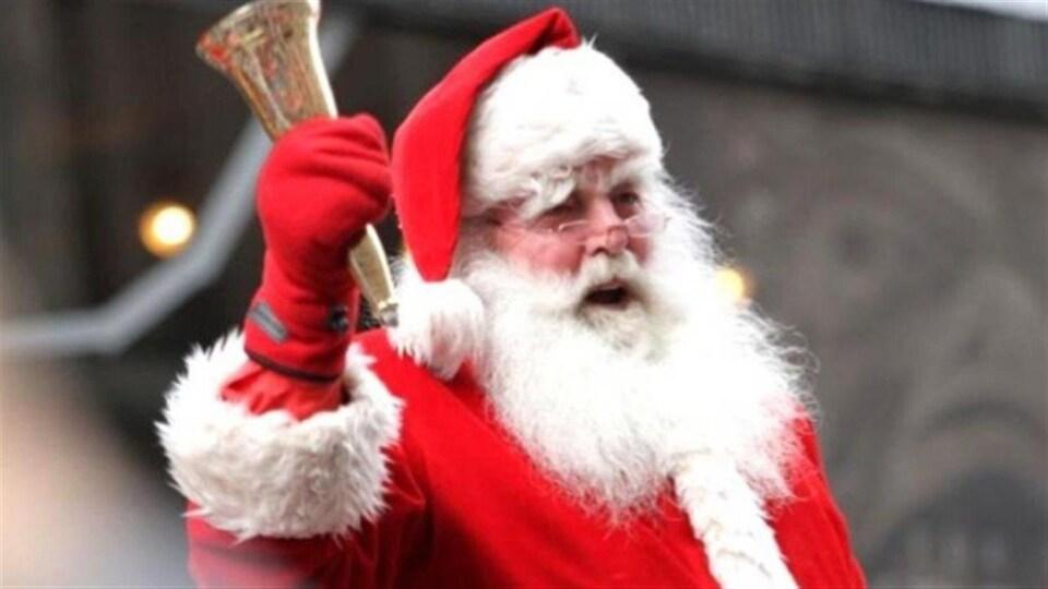 Un père Noël agite une cloche dans les airs.