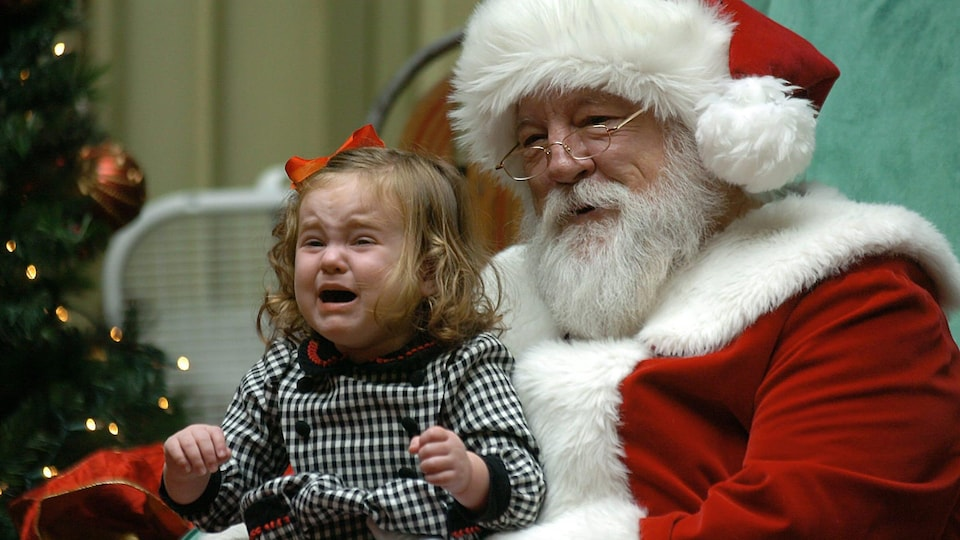 Une fillette pleure en se faisant prendre en photo sur les genoux du père Noël.