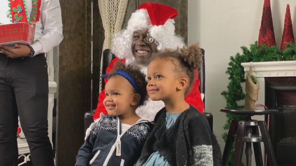 Le père Noël prend la pause avec deux enfants aux regards brillants.
