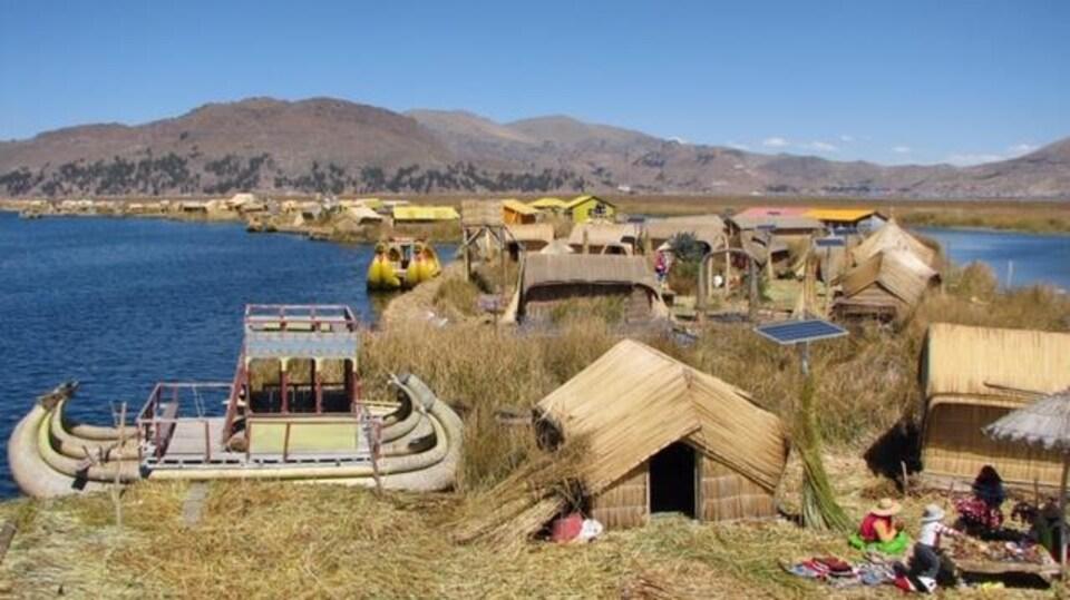 Une île et ses habitations faites de bois et de paille, avec le le lac et des montagnes en arrière-plan.