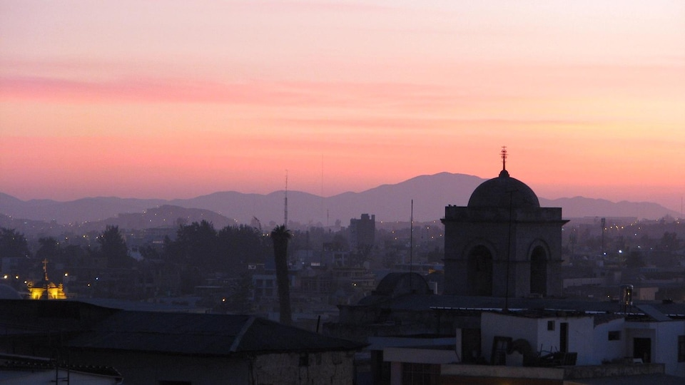 Un ciel rosé surplombe la silhouette d'une ville entourée de montagnes alors que le soleil se couche.