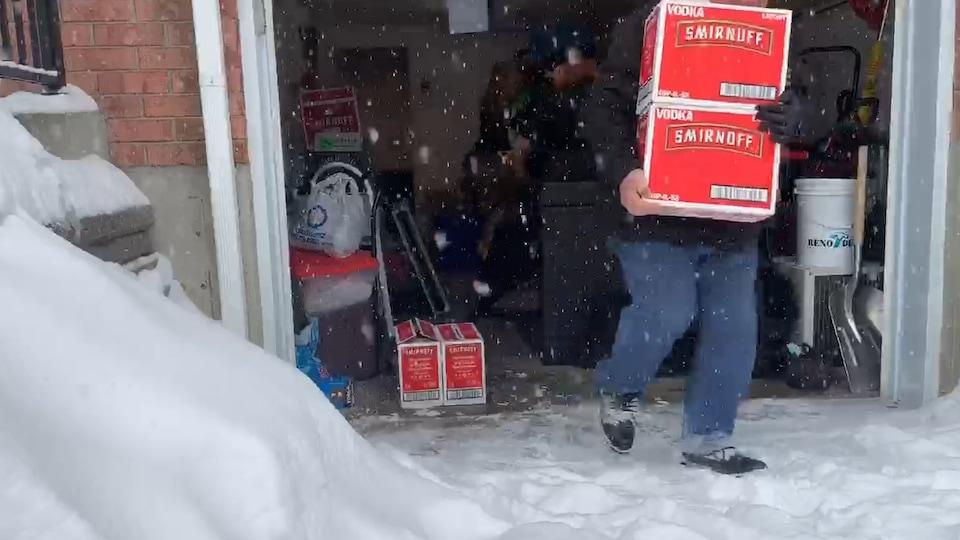 Des hommes sortent des caisses de vodka Smirnoff d'un garage.