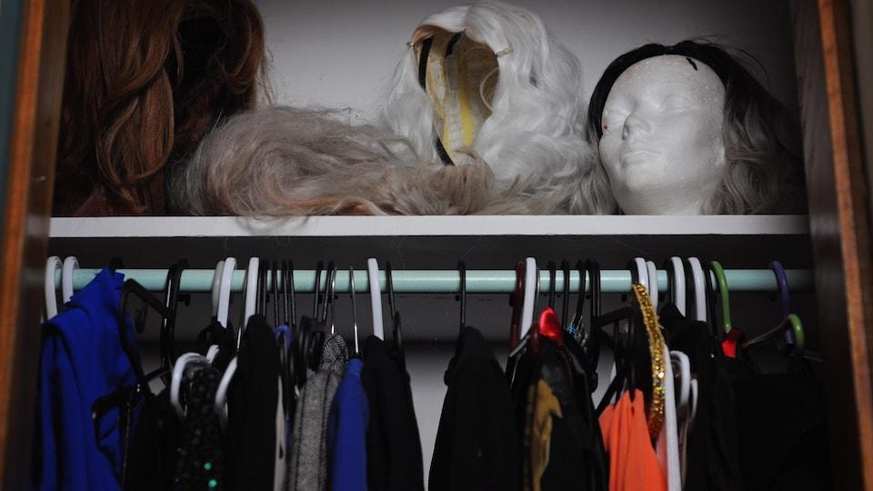 Une garde-robe avec des perruques et des robes.
