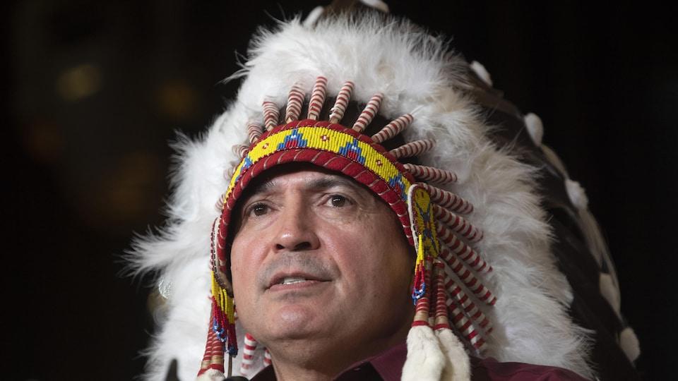 Gros plan sur le visage de Perry Bellegarde, qui porte la coiffe traditionnelle à plumes.