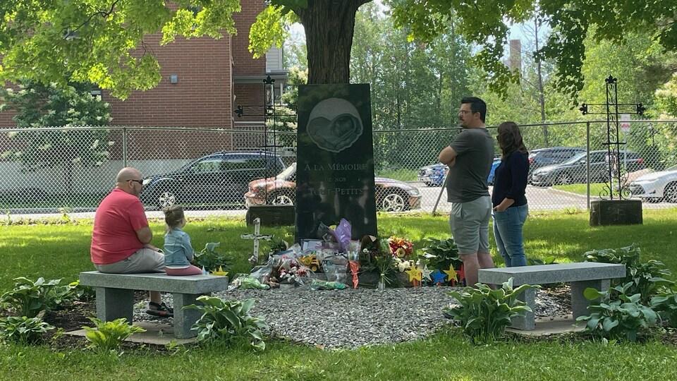 Des parents autour d'un monument commémoratif.