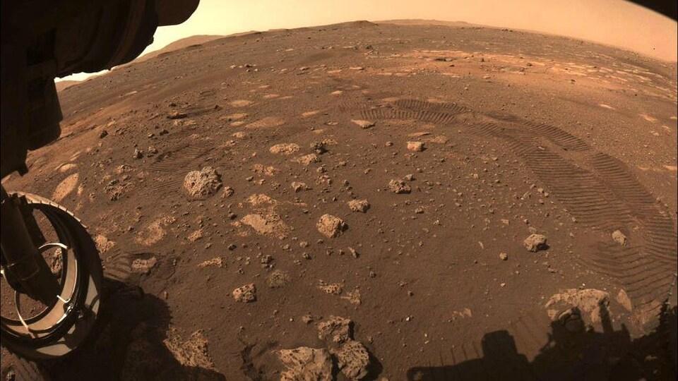 Sur le sol ocre de la planète Mars, on voit des cailloux et des traces de roues.