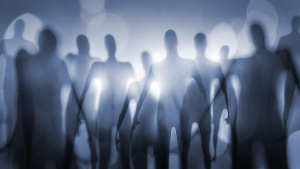 Des silhouettes floues de plusieurs personnes.