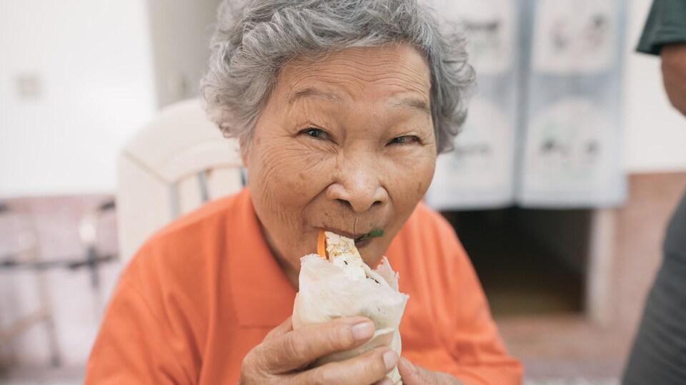 Une dame mange un rouleau de printemps.