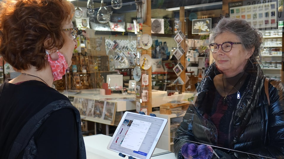 Une femme au comptoir d'un commerce discute avec une autre femme derrière le comptoir