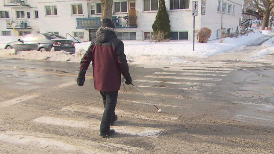 Un homme souffrant de déficience visuelle traverse une rue à l'aide d'une canne.