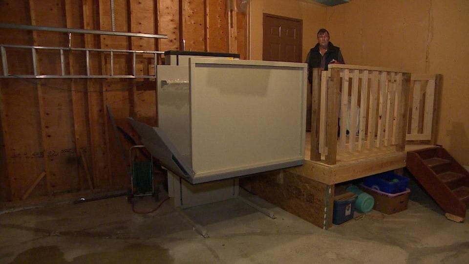 Un homme près d'un ascenseur pour fauteuils roulants dans un garage.