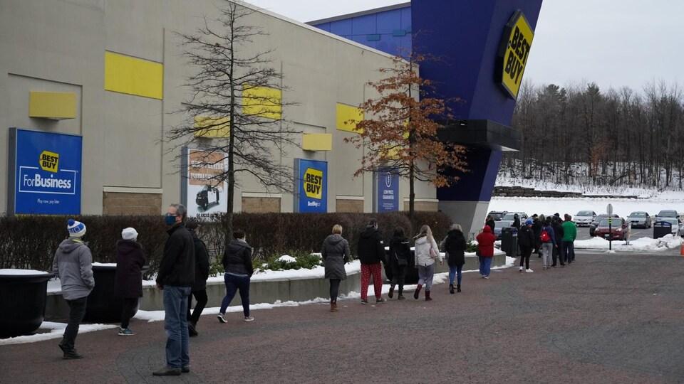 Des personnes font la file à l'extérieur d'un magasin.