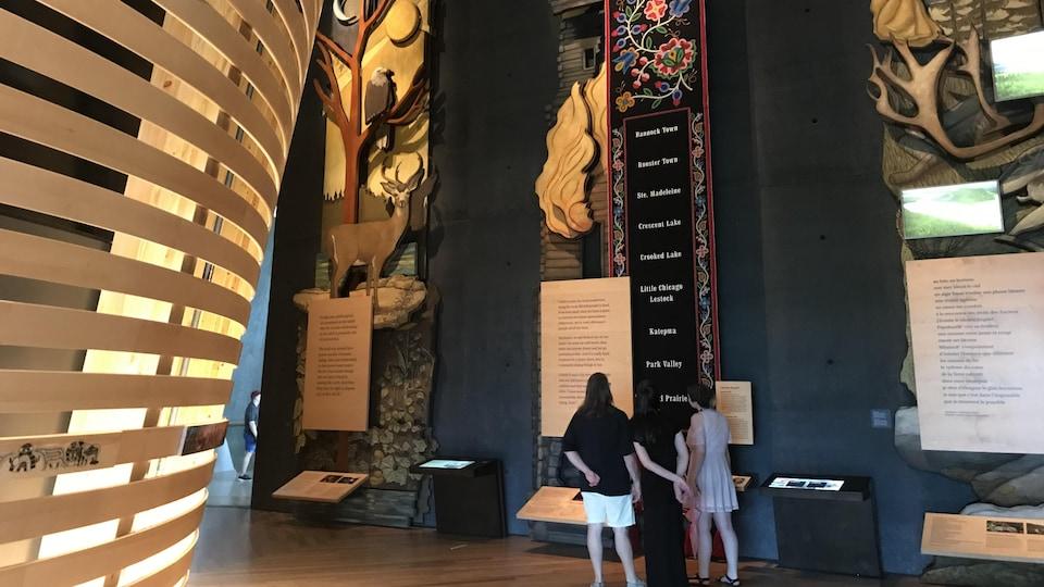 Trois visiteuses devant une grande oeuvre de perles dans une galerie d'un musée.