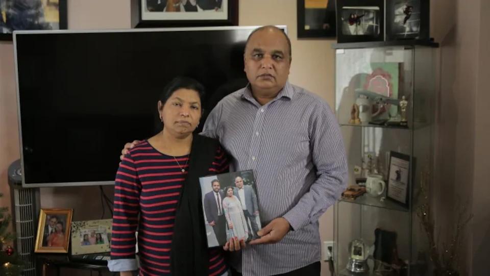 Un homme et une femme dans un salon posent avec une photo de famille.