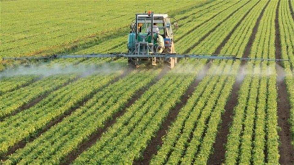 Un tracteur répand des pesticides.