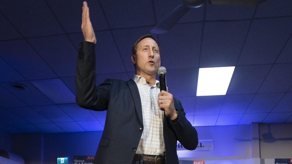 Peter MacKay tient un micro de la main gauche et lève la droite bien haut.