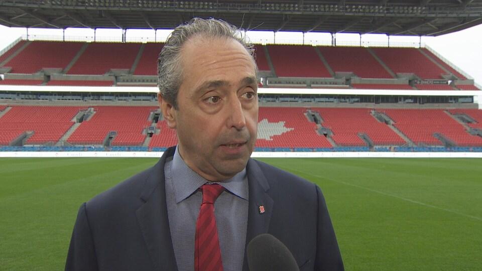 Le secrétaire général de l'Association canadienne de soccer, Peter Montopoli répond au micro de Radio-Canada au BMO Fiedl de Toronto. Il a les cheveux gris, un veston bleu marine, une crave rouge avec des rayures bordeaux.